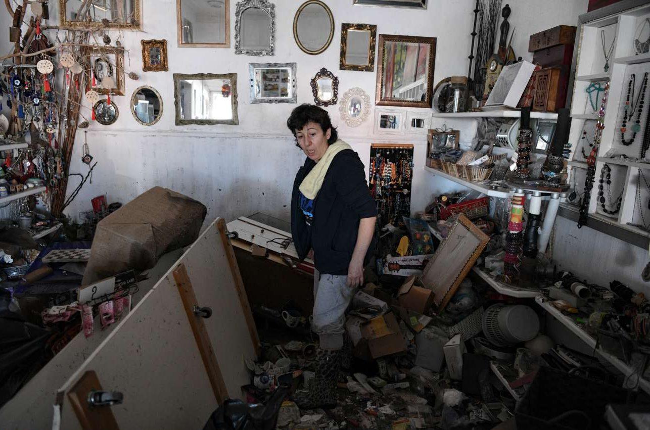 Μια γυναίκα στέκεται στο διαλυμένο μαγαζί της μετά το πέρασμα του Εγκέλαδου στη Σάμο