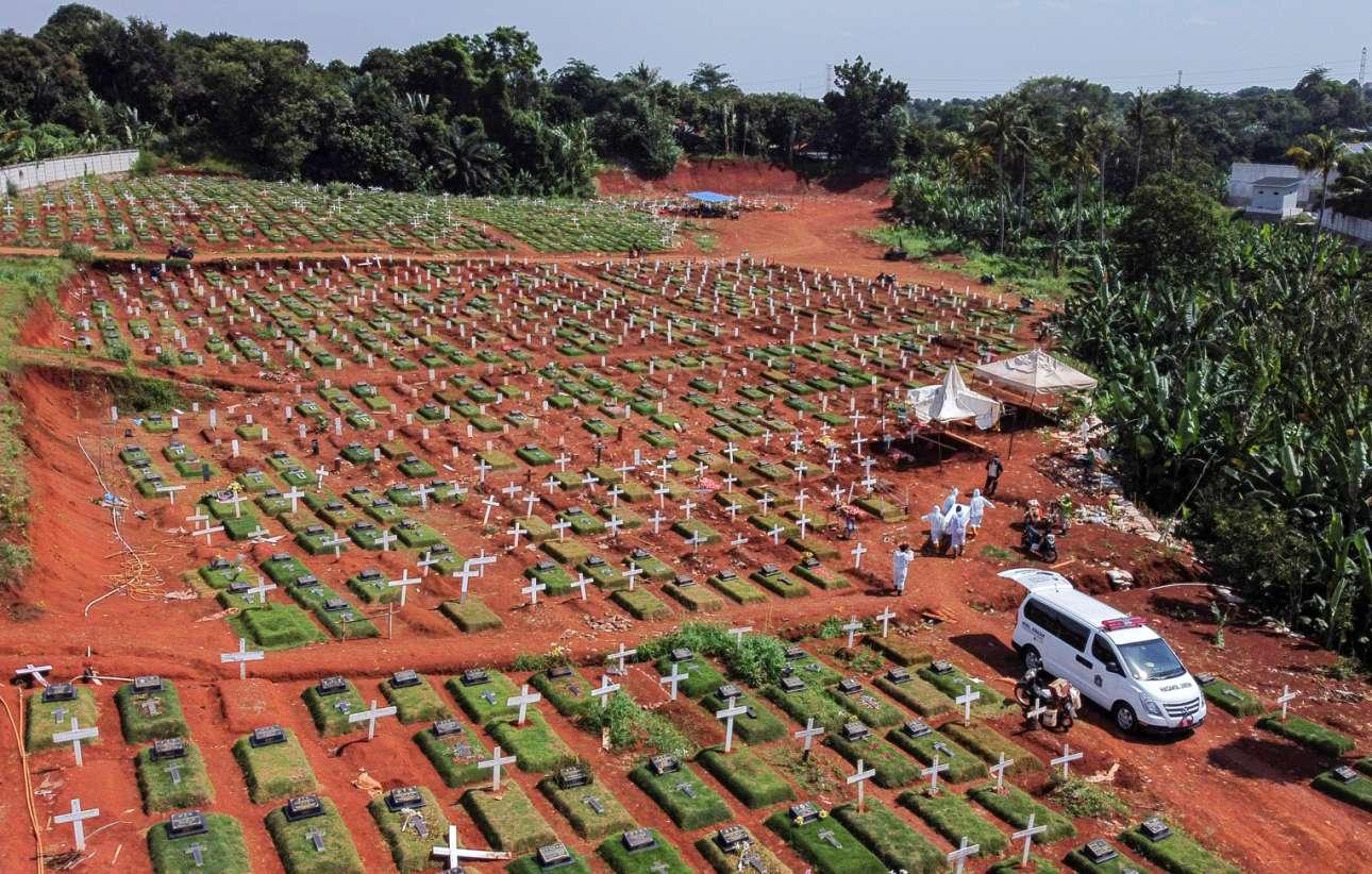 Νεκροταφείο θυμάτων του κορονοϊού στην Τζακάρτα της Ινδονησίας. Οι εργάτες, ντυμένοι με υγειονομικές στολές, μεταφέρουν το φέρετρο κάποιου. Δεν ήταν ο Μαραντόνα, αλλά κάποιος θα τον έκλαψε και αυτόν