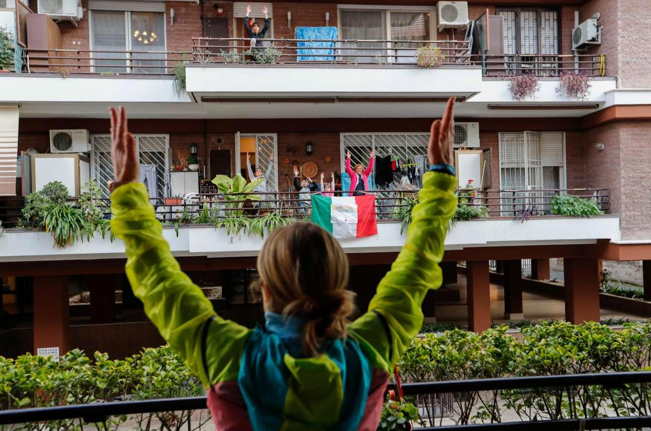 Μάρτιος, Ιταλία: η personal trainer Αντονιέτα Ορσίνι παραδίδει μαθήματα γυμναστικής στους γείτονες της από την ασφάλεια του σπιτιού της στη Ρώμη