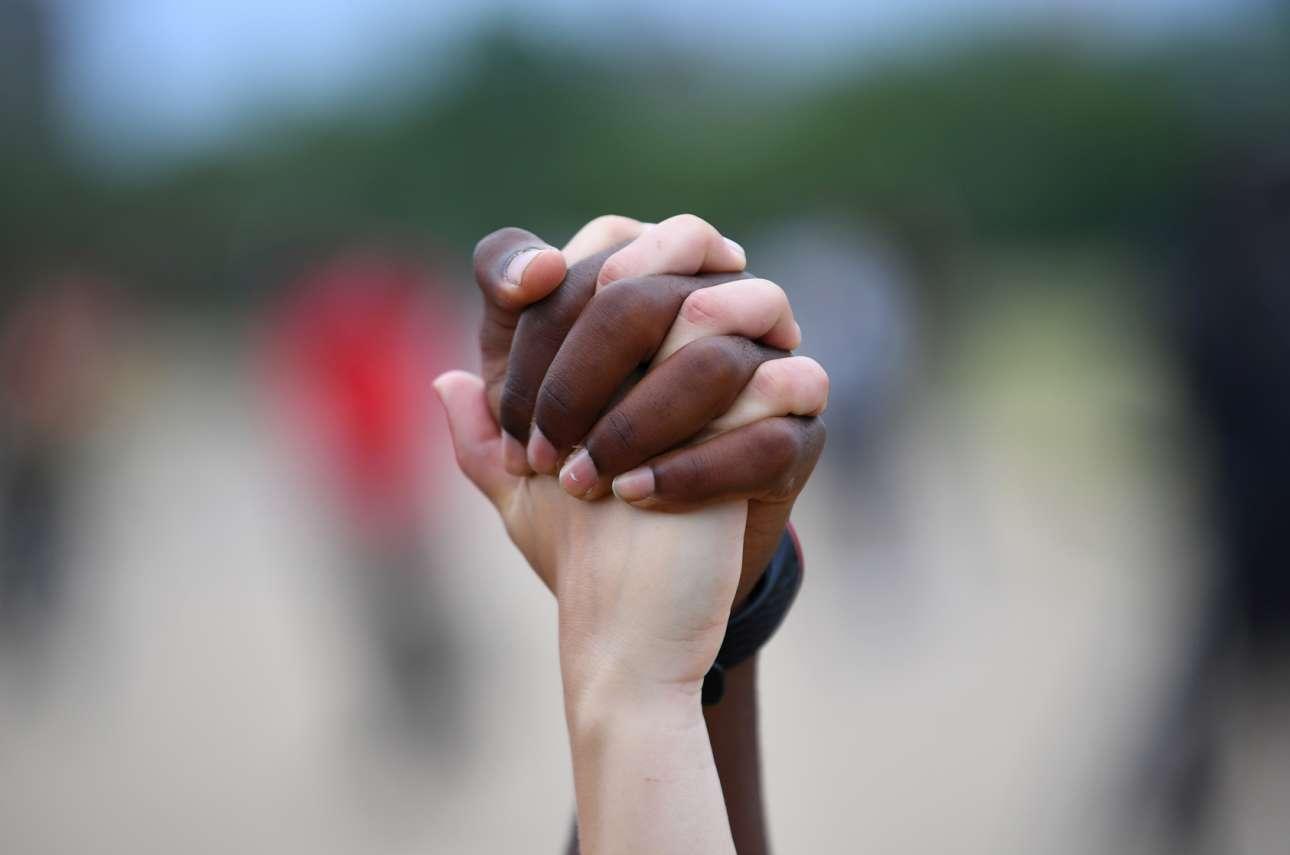 Ιούνιος, Λονδίνο. Συμβολική χειρονομία υπέρ της φυλετικής ισότητας και συναδέλφωσης στο λονδρέζικο Χάιντ Παρκ κατά τη διάρκεια μιας διαδήλωσης Black Lives Matter