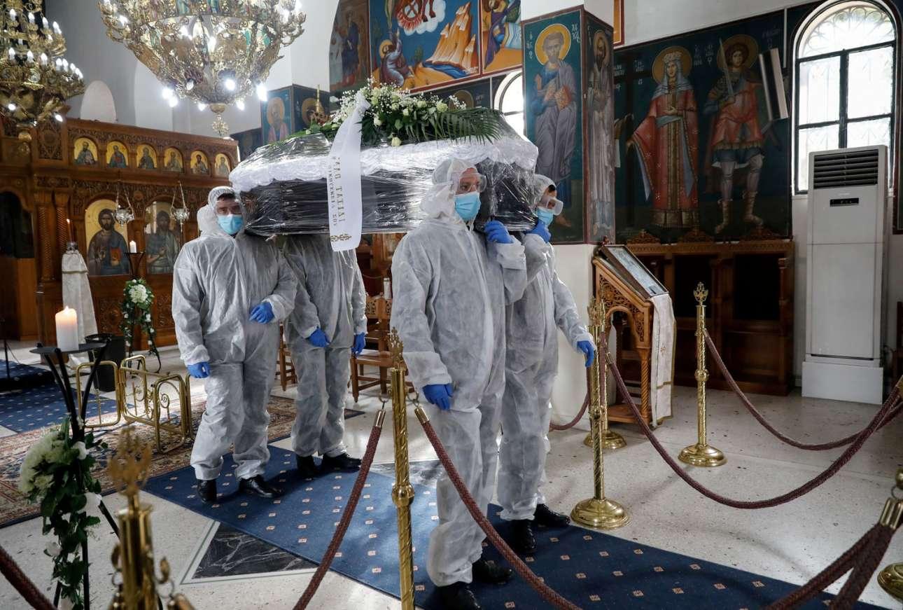 Νεκροπομποί ντυμένοι με ειδικές προστατευτικές σχολές μεταφέρουν το φέρετρο κάποιου θανόντος από κορονοϊό – στιγμιότυπο από ναό αττικού κοιμητηρίου