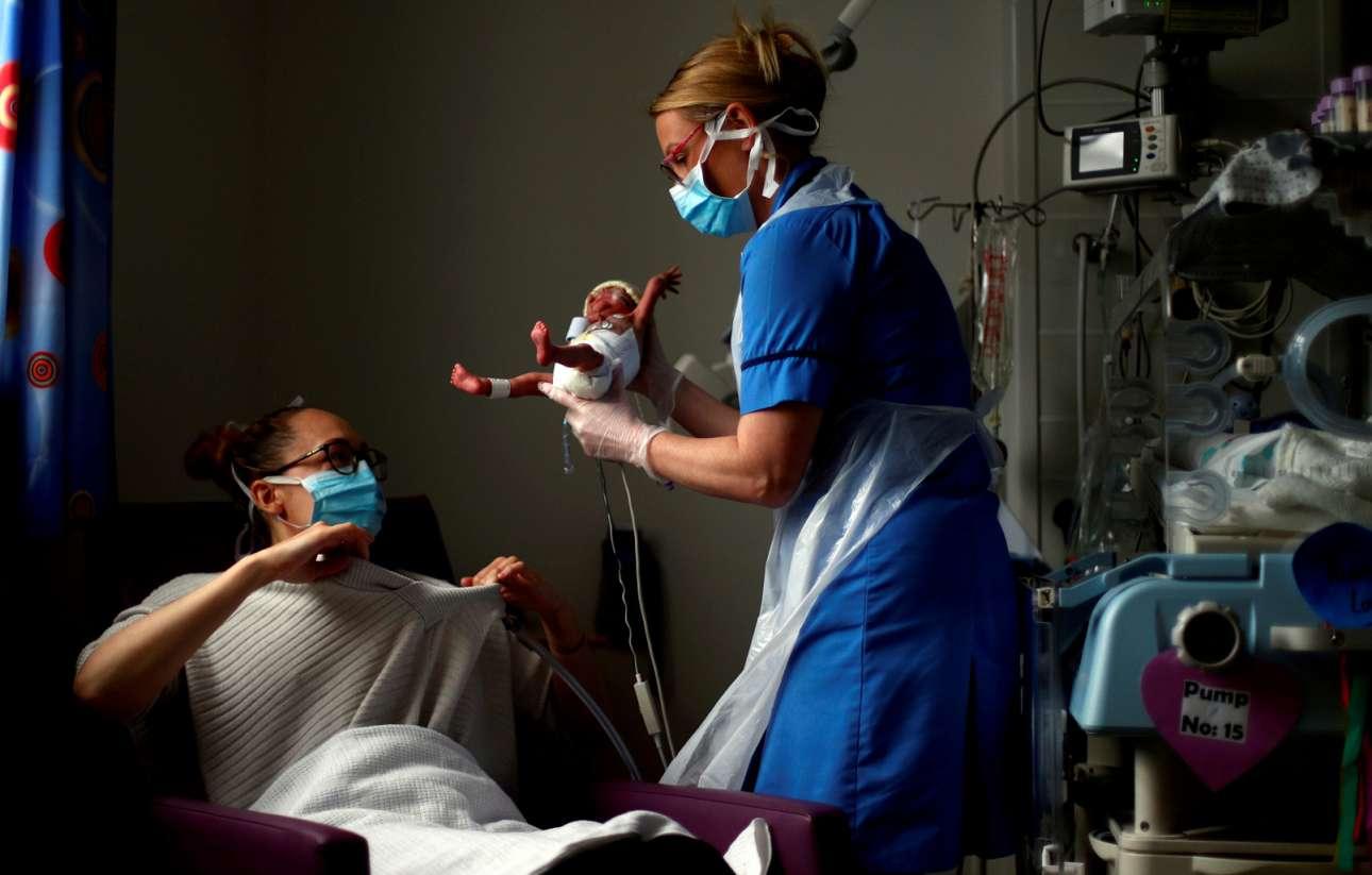 Το θαύμα της γέννησης στον καιρό της πανδημίας. Η νοσοκόμα Κέρστι Χάρτλεϊ κρατά στα χέρια της τον μικροσκοπικό Τέο Αντερσον που γεννήθηκε πρόωρα στην μονάδα εντατικής θεραπείας νεογνών στο Γενικό Νοσοκομείο του Μπέρνλι του Ηνωμένου Βασιλείου