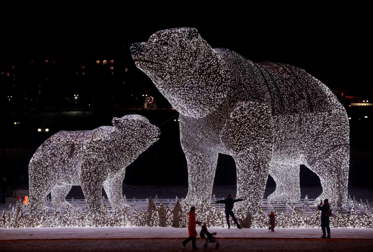 Μοσχοβίτες θαυμάζουν σε ένα χιονισμένο πάρκο την εποχικού χαρακτήρα υπερμεγέθη «εγκατάσταση» σε σχήματα πολικών άρκτων (μαμά και μωρό), η οποία απαρτίζεται από χιλιάδες λευκά φωτάκια.