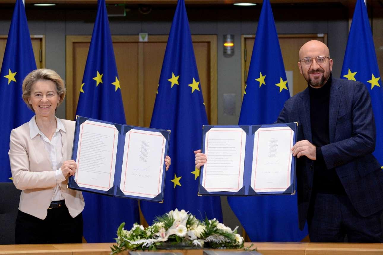 Φαίνονται χαρούμενοι: η πρόεδρος της Κομισιόν Ούρσουλα φον ντερ Λάιεν και ο πρόεδρος του Ευρωπαϊκού Συμβουλίου Σαρλ Μισέλ δείχνουν στον φακό την εμπορική συμφωνία του Brexit που συνυπέγραψαν με τους Βρετανούς και η οποία θα ισχύσει από 1ης Ιανουαρίου