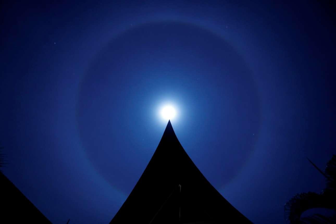 Εξωτικό δακτύλιο γύρω από το ολόγιομο φεγγάρι συνέλαβε ο φακός στην Ταϊλάνδη. Το φαινόμενο το λένε και «χειμερινή άλω», μας πληροφορεί η λεζάντα του πρακτορείου. Οι σκοτεινοί όγκοι είναι στέγες παραδοσιακών σπιτιών δίπλα σε αναλόγως εξωτική παραλία