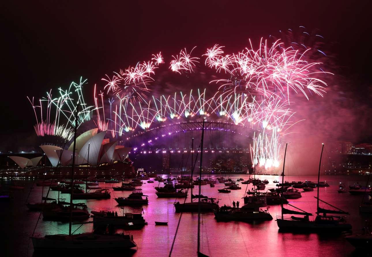 Πρωτοχρονιά στο Σίδνεϊ, στο μέρος όπου ο καινούργιος χρόνος εισβάλλει νωρίτερα: ροζ και πράσινα πυροτεχνήματα άστραψαν πάνω από το κτίριο της όπερας και τη γέφυρα του λιμανιού, ενώ ο κόσμος χάζευε από τα ιστιοπλοϊκά