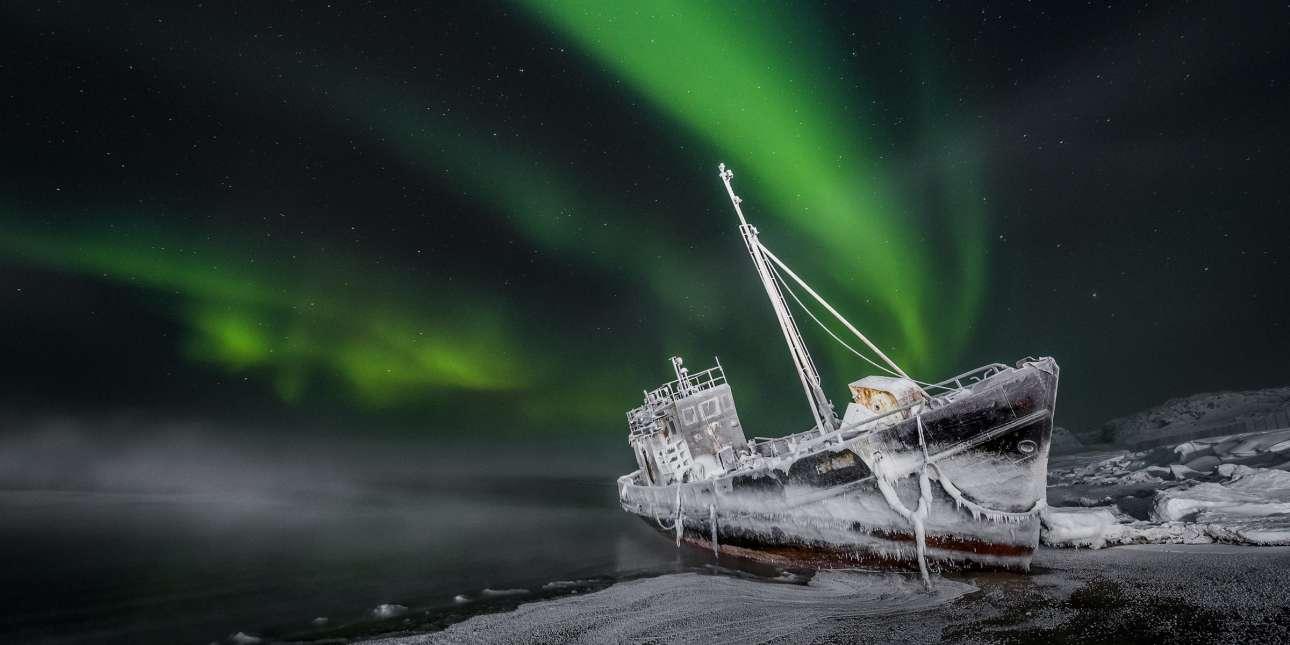 Κάτω από το αστέρι του Βορρά. Eνα παγωμένο κουφάρι πλοίου που έχει ξεβραστεί σε μια ακτή του Mουρνμάσκ, στη Θάλασσα Μπάρεντς, στην Ρωσία υπό το «βλέμμα» του πολικού αστέρα και ενώ εξελίσσεται το βόρειο σέλας. Η φωτογραφία κέρδισε το δεύτερο βραβείο στην κατηγορία ερασιτεχνών φωτογράφων
