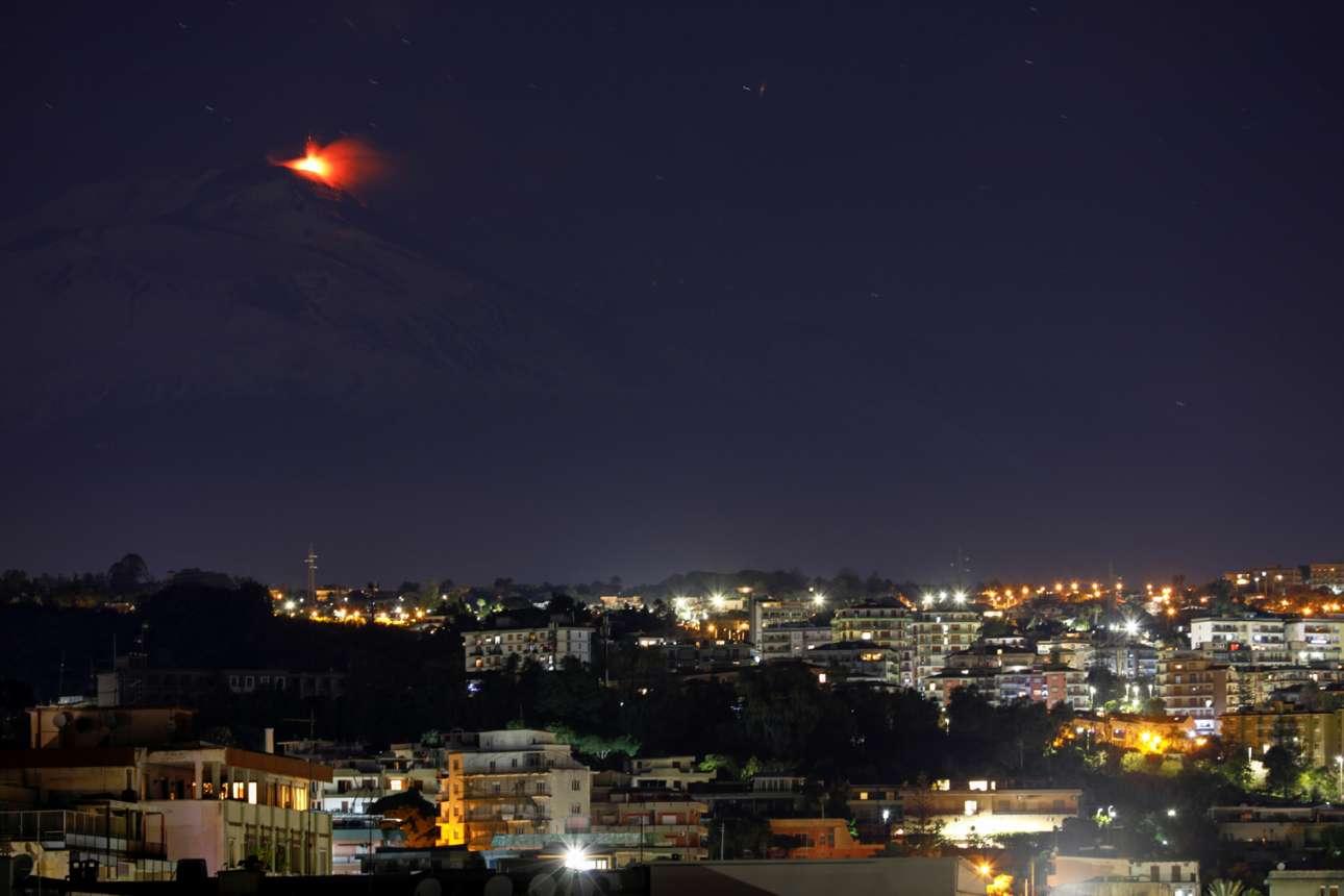 Εδώ κάτω είναι η Κατάνια και εκεί ψηλά είναι η Αίτνα. Η πόλη κοιμάται, το ηφαίστειο ξυπνά. Μία ωραία αν και διόλου σπάνια φωτιά μέσα στη σικελική νύχτα