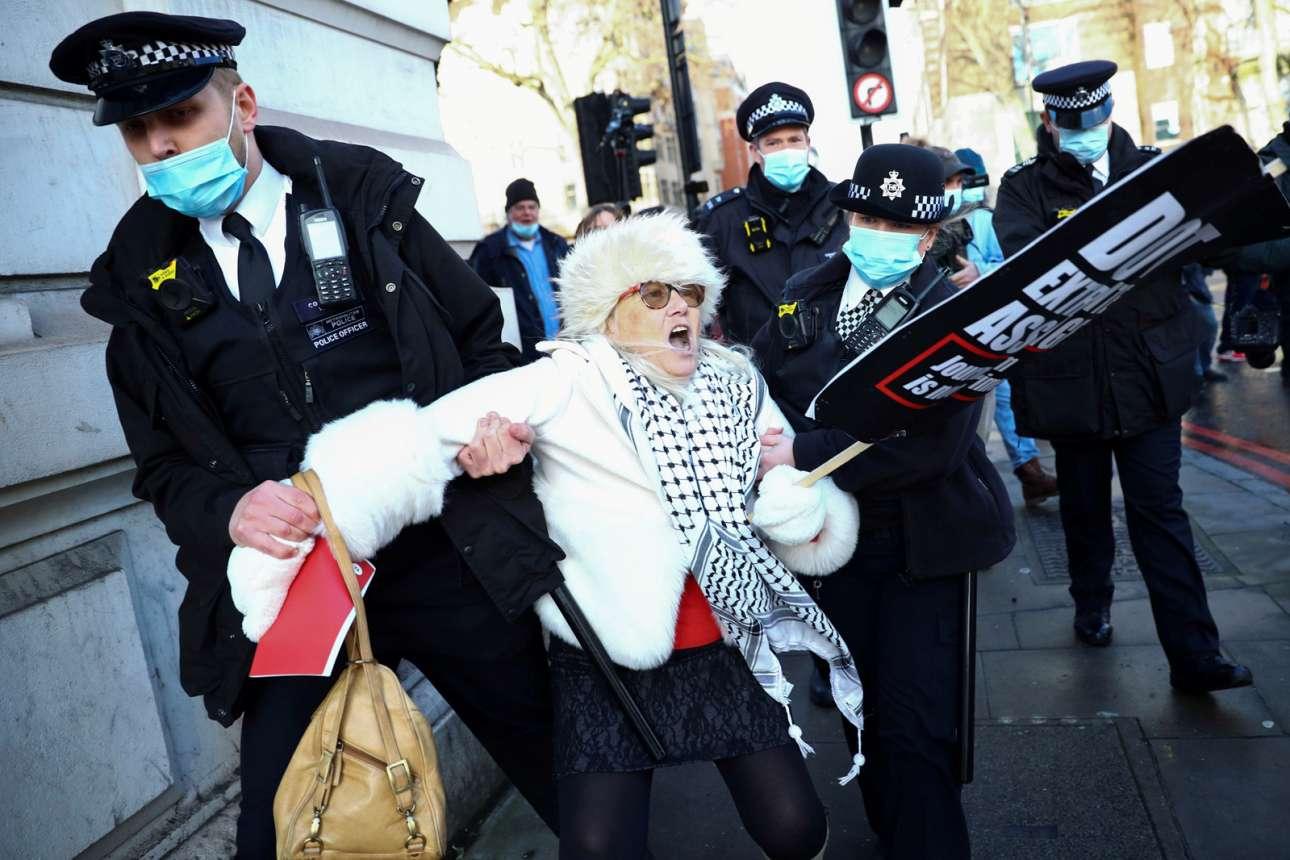 Αστυνομικοί συλλαμβάνουν έξω από το λονδρέζικο δικαστήριο κάποια που διαδηλώνει με πάθος κατά της έκδοσης του Τζούλιαν Ασάνζ
