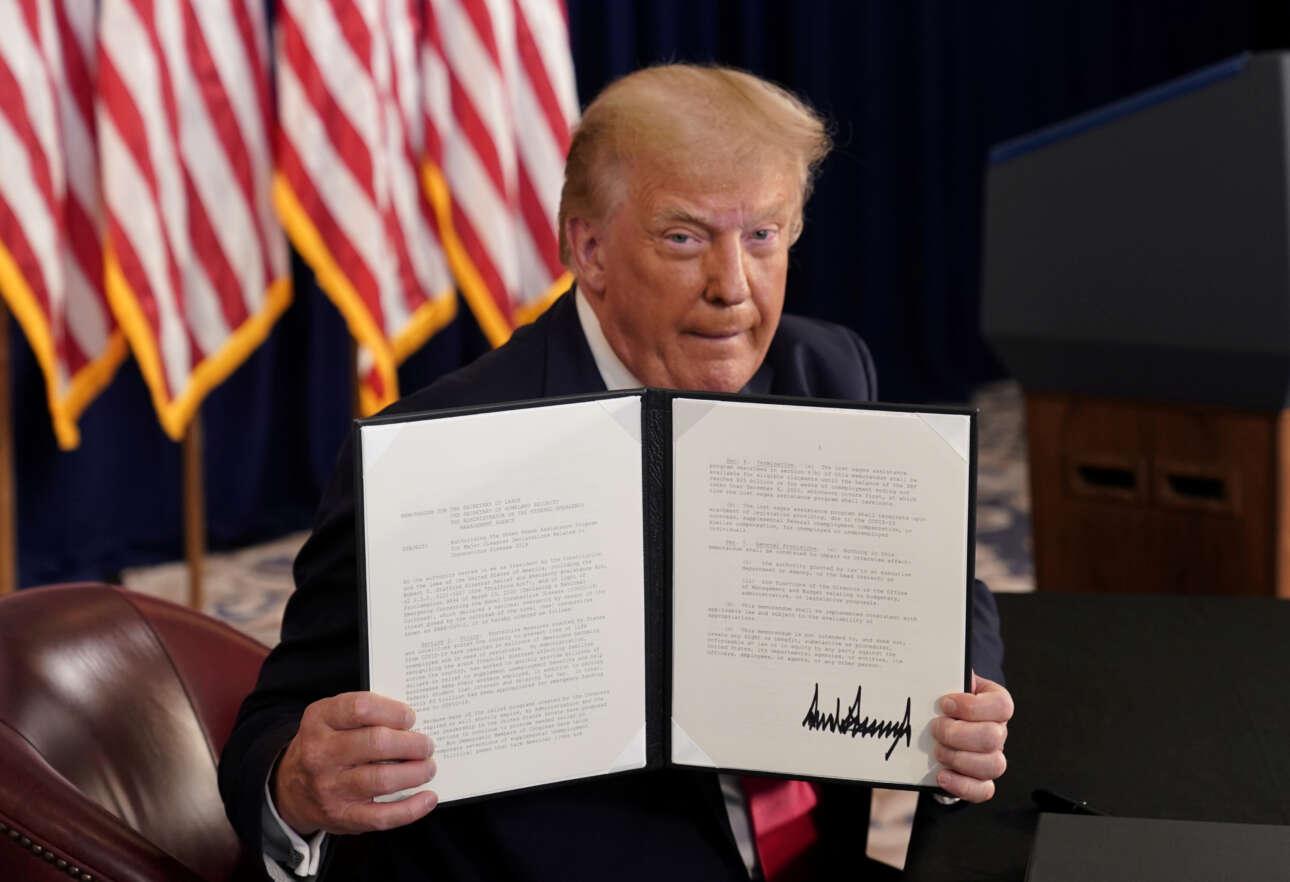 Αύγουστος 2020. Ο Ντόναλντ Τραμπ επιδεικνύει προεδρικά διατάγματα που υπέγραψε για οικονομική βοήθεια σε πληγέντες από την πανδημία. Τα υπέγραψε στο θέρετρό του στο Νιού Τζέρσεϊ, κάνοντας ένα διάλειμμα από το παιχνίδι γκολφ
