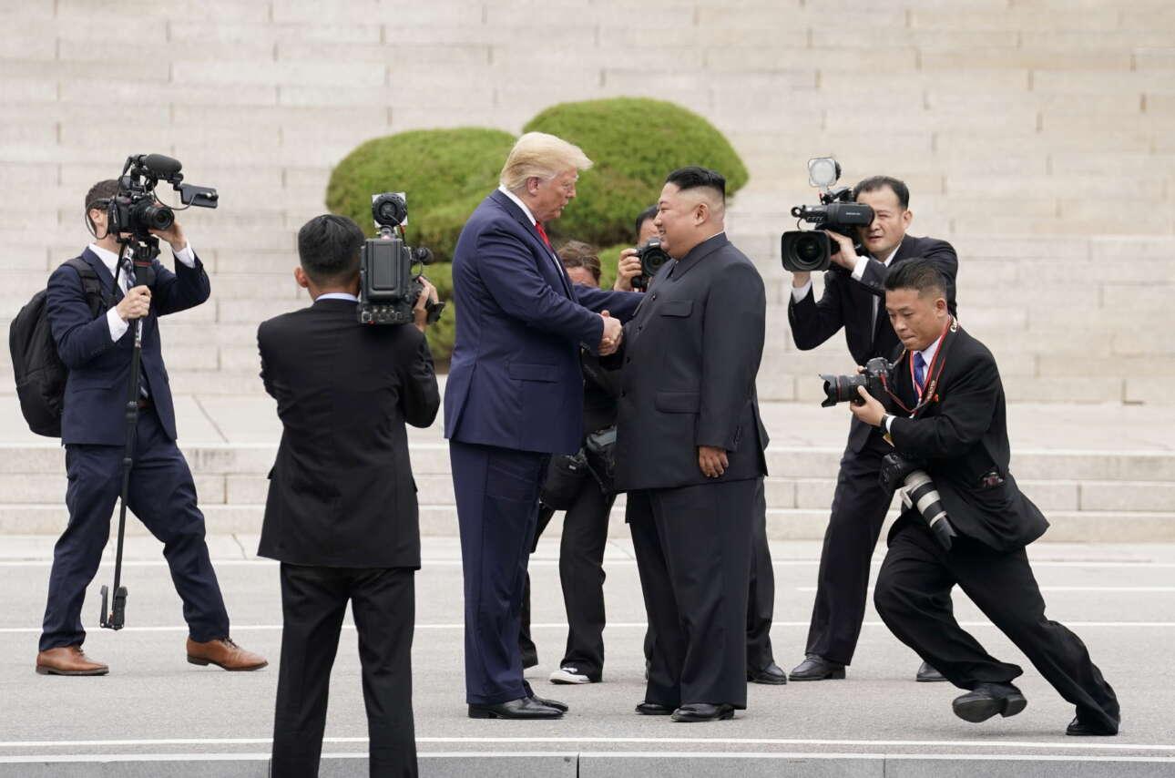 Ιούνιος 2019. Μια χορογραφία λιγοστών εικονοληπτών και φωτορεπόρτερ καθώς ο Ντόναλντ Τραμπ συναντά στην αποστρατικοποιημένη ζώνη της κορεατικής χερσονήσου τον βορειοκορεάτη δικτάτορα Κιμ Γιόνγκ Ουν. «Η γωνία του φωτογράφου δεξιά μαρτυρά την αγωνία των στιγμών», θα πει ο Κέβιν Λαμάρκ του Reuters που έπιασε το κάδρο
