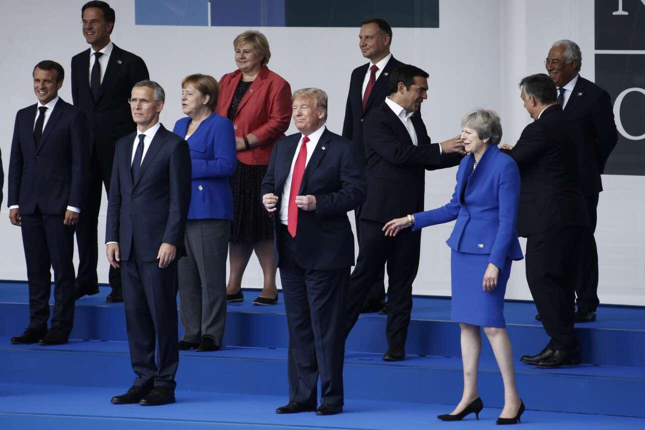 Ιούλιος 2018. Οι οικογενειακές φωτογραφίες είναι πάντα άχαρες. Η Τερέζα Μέι προσπαθεί να δώσει το χέρι της στον Τραμπ που στήνεται για τους φωτογράφους. Πίσω τους διακρίνεται ο τότε Πρωθυπουργός Αλέξης Τσίπρας