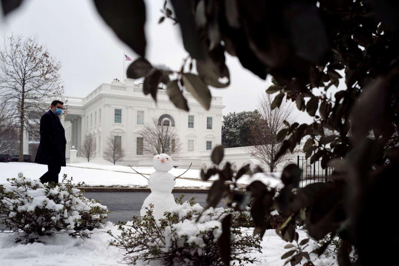 Ανδρας περνά και κοιτάζει ένα χιονάνθρωπο που έχει στηθεί στην αυλή του Λευκού Οίκου