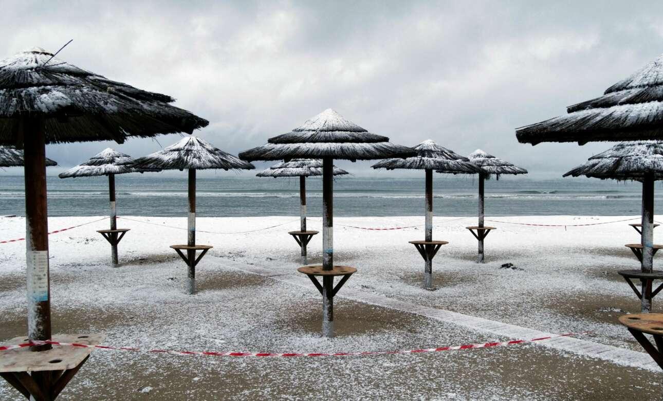 Η παραλία της Αρτέμιδας χιονισμένη. Η ασπροκόκκινη κορδέλα στέκεται για να μας υπενθυμίζει ότι μέτρα κατά του κορονοϊού συνεχίζουν να ισχύουν