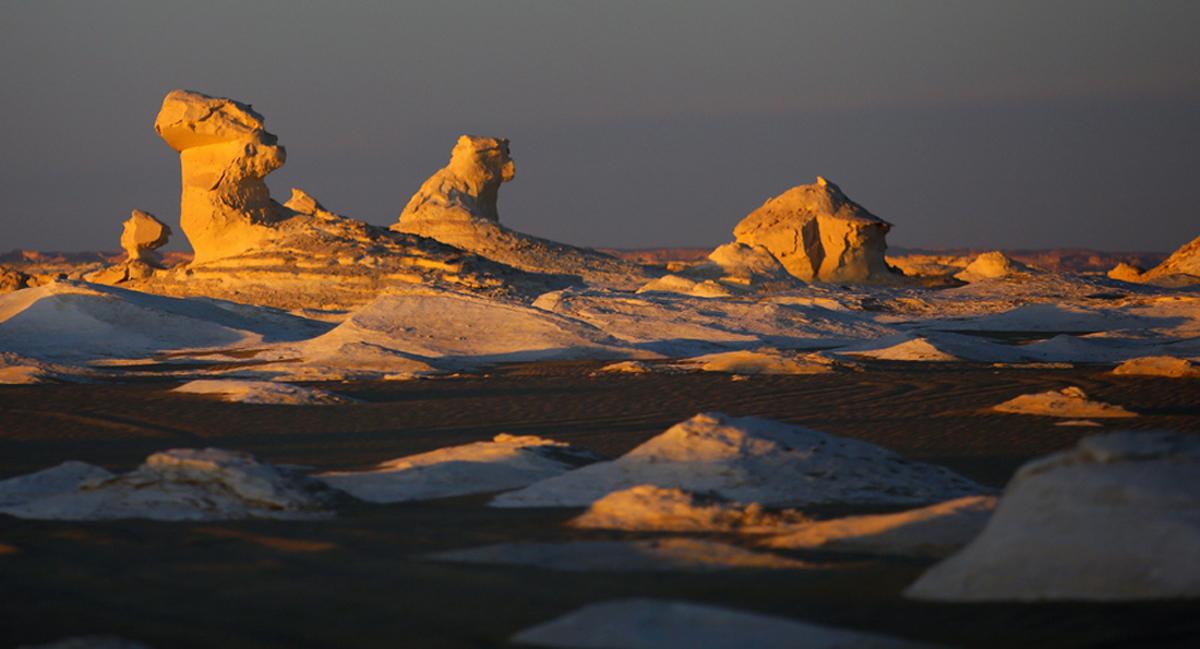 O ήλιος δύει πίσω από τους παράξενους σχηματισμούς βράχων στην Λευκή Ερημο