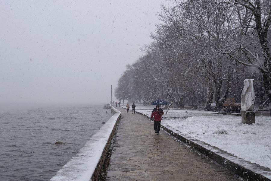 Κόσμος κάνει την βόλτα του εν μέσω χιονόπτωσης στην λίμνη των  Ιωαννίνων