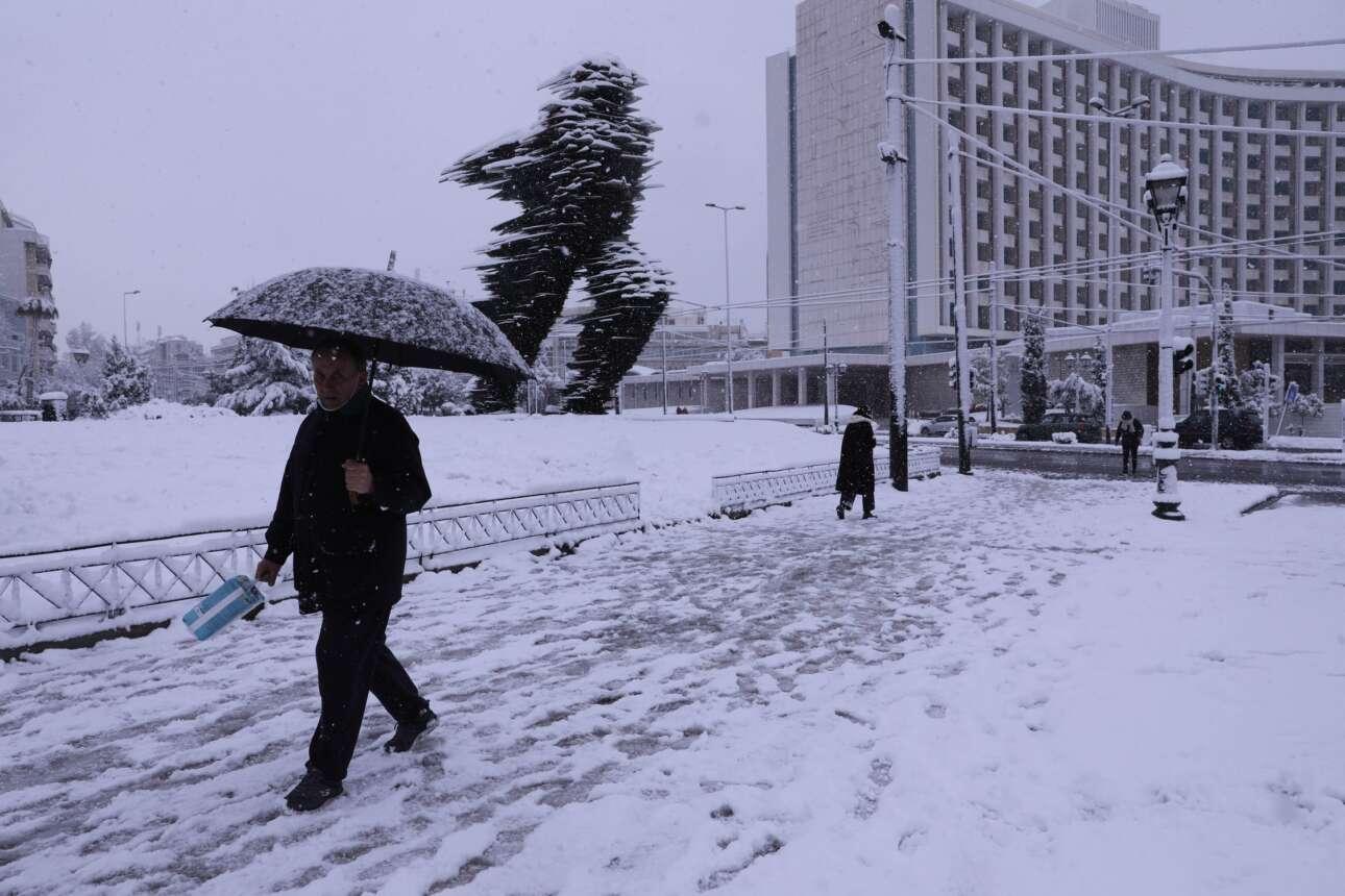 Οι λίγοι περιπατητές προσπερνούν τον σκεπασμένο από το χιόνι Δρομέα απέναντι από το Χίλτον