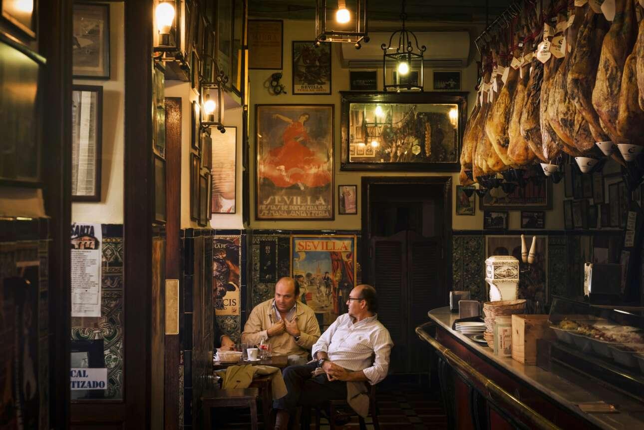 Ειδική Μνεία, κατηγορία Ταξιδιωτικό Πορτφόλιο. Μπαρ Las Teresas, Σεβίλλη, Ισπανία. «Τρεις άντρες κάθονται σε ένα μικρό τραπέζι συνομιλώντας έντονα, ανάμεσα σε παλιές αφίσες, πίνακες ζωγραφικής, πιάτα και καλάθια για φαγητό και μια σειρά κρεμασμένου κρέατος χαμόν πάνω από τον πάγκο»