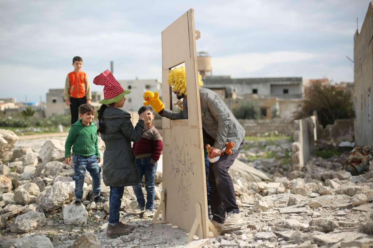 Ειδική Μνεία στην κατηγορία Ανθρωποι του Κόσμου.  Από το 2013, ο Γαλίντ Ρασίντ περιοδεύει σε στρατόπεδα προσφύγων και κατεστραμμένες γειτονιές παίζοντας κουκλοθέατρο και θέατρο σκιών για τα παιδιά της Συρίας. Στη φωτογραφία, ο Ρασίντ δίνει παράσταση με μαριονέτες σε επίσκεψή του στη Σαρακέμπ, με αφορμή την Παγκόσμια Ημέρα του Θεάτρου