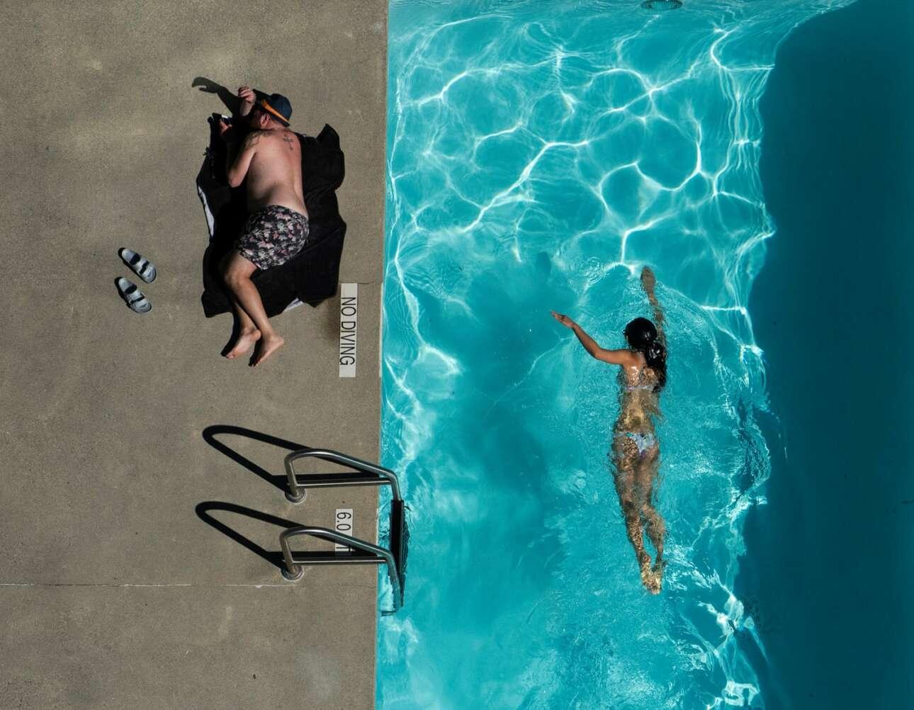 Ειδική Μνεία στην κατηγορία Ανθρωποι του Κόσμου. «Στην εξωτερική πισίνα του διαμερίσματος, το κορίτσι κολυμπά ενώ δίπλα ο άντρας κάνει ηλιοθεραπεία, δημιουργώντας έτσι μια ενδιαφέρουσα αντίθεση ανάμεσα στις δύο φιγούρες. Το φως που μπαίνει ανάμεσα από τα κτίρια δημιουργεί ένα ειδικό φωτιστικό εφέ στο νερό. Η φωτογραφία τραβήχτηκε από τον 29ο όροφο»