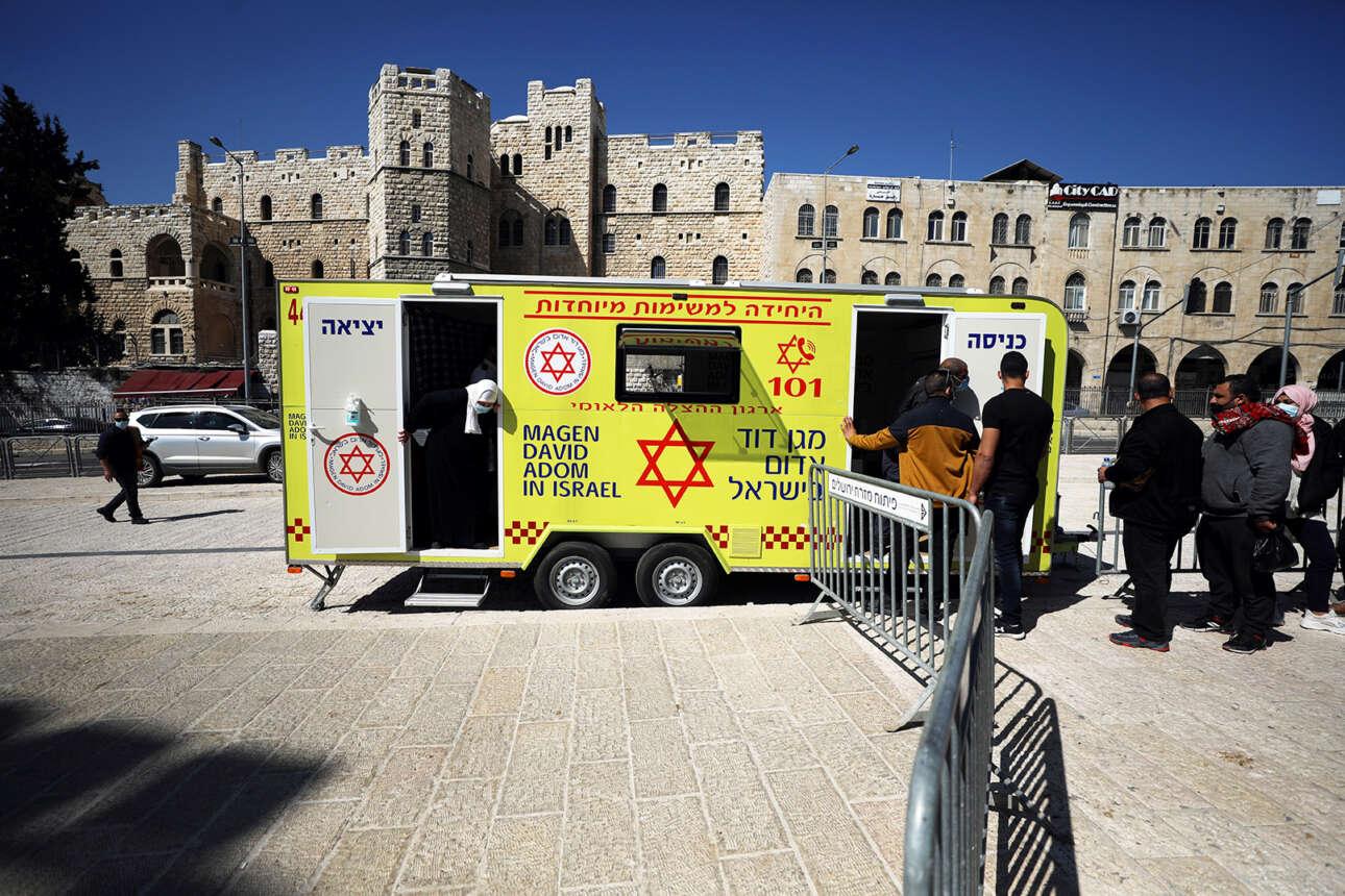 Στην Ιερουσαλήμ, άνθρωποι περιμένουν στην ουρά για εμβολιασμό κατά της COVID-19 έξω από ένα κινητό όχημα εμβολιασμού