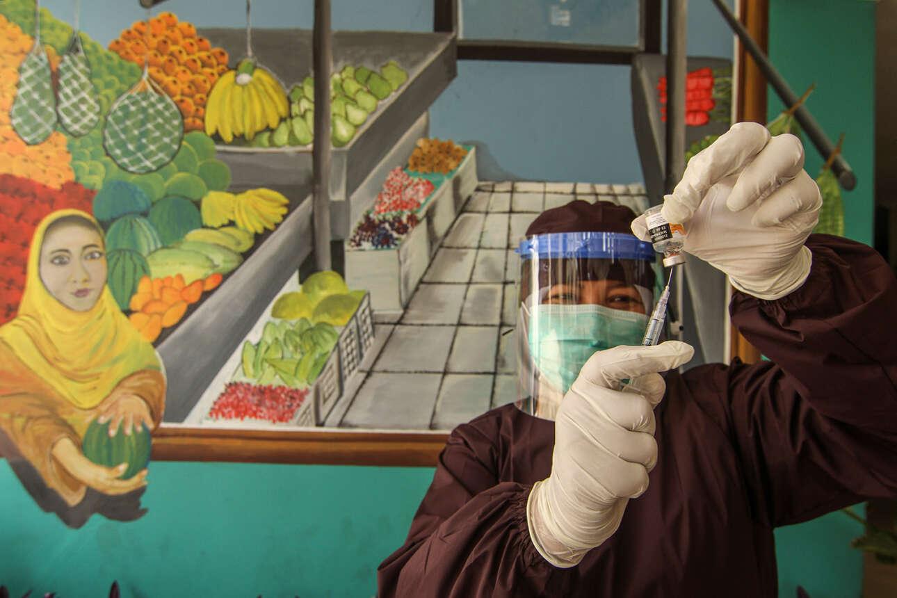 Στην Ινδονησία, υγειονομικός υπάλληλος προετοιμάζει μια δόση του κινεζικού εμβολίου της Sinovac κατά τη διάρκεια ενός προγράμματος μαζικού εμβολιασμού για πωλητές σε παζάρι στο Ντεπόκ, στα περίχωρα της Τζακάρτα