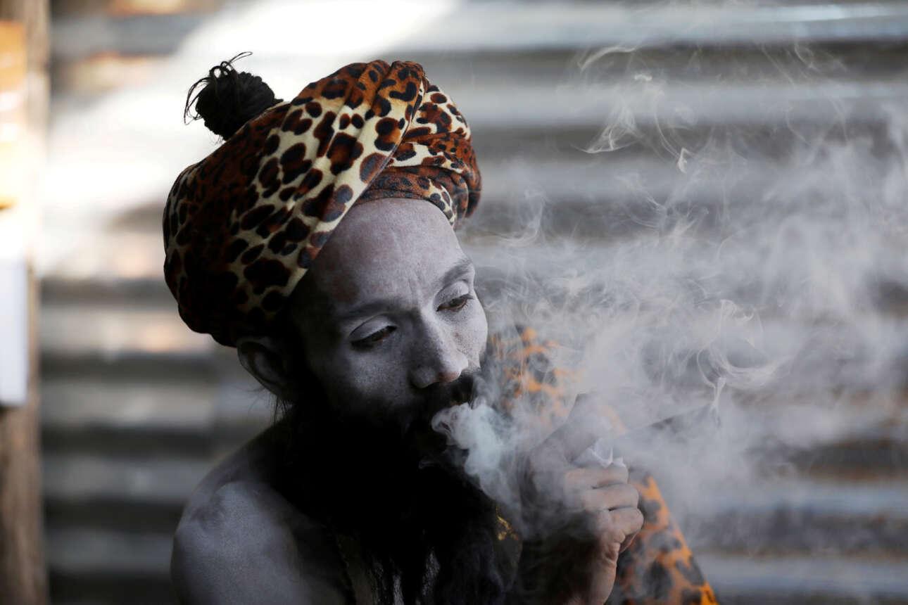 Ινδουιστής «άγιος άνθρωπος» καπνίζει αρειμανίως μέσα στο τσαντίρι του συμμετέχοντας στο θρησκευτικό φεστιβάλ Κούμπα Μέλα