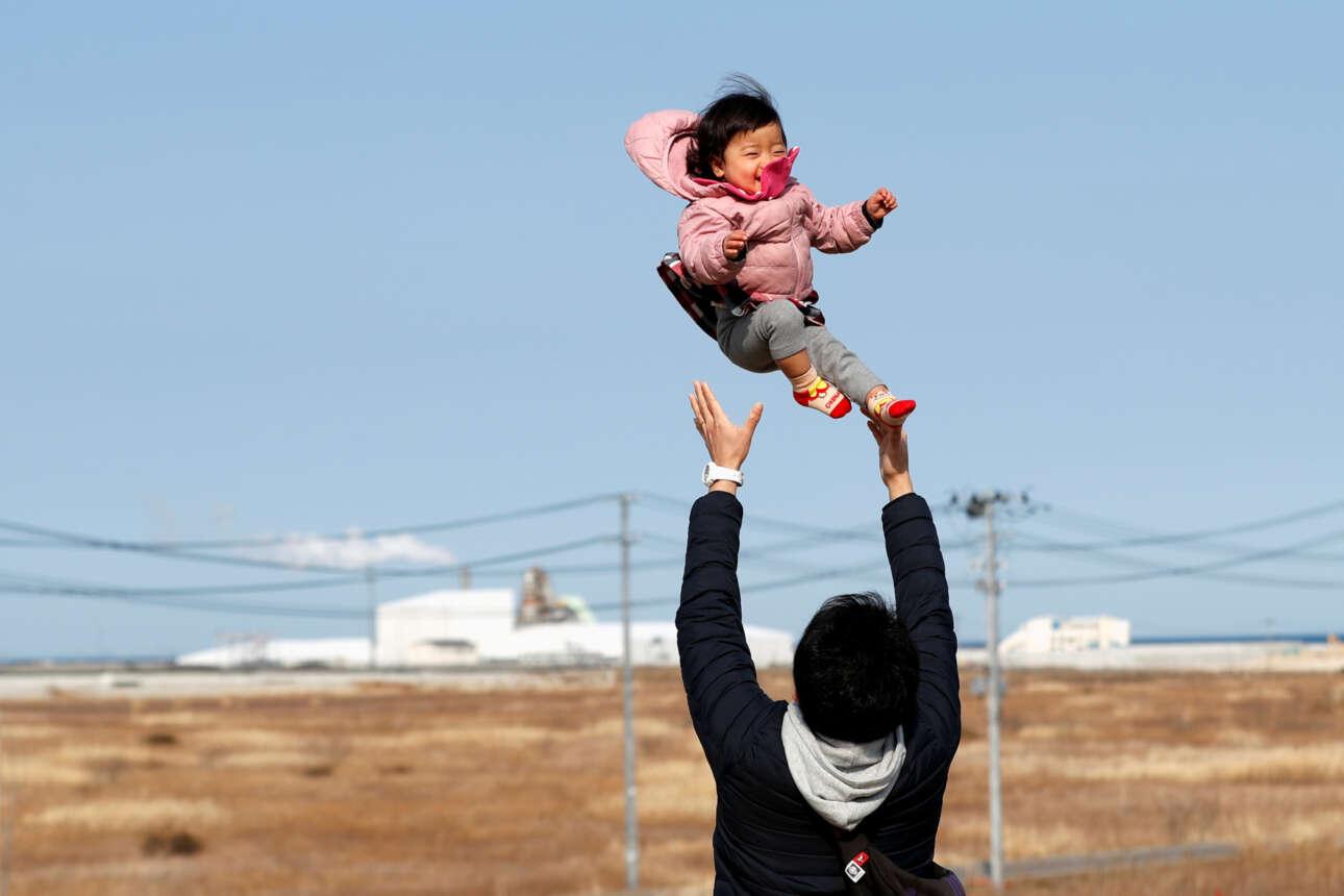 Στη σχεδόν έρημη πια Φουκουσίμα, να και λίγη ανθρωπιά: ένας χαροκαμένος στην καταστροφή του 2011 άνδρας παίζει ανέμελα με την κορούλα του