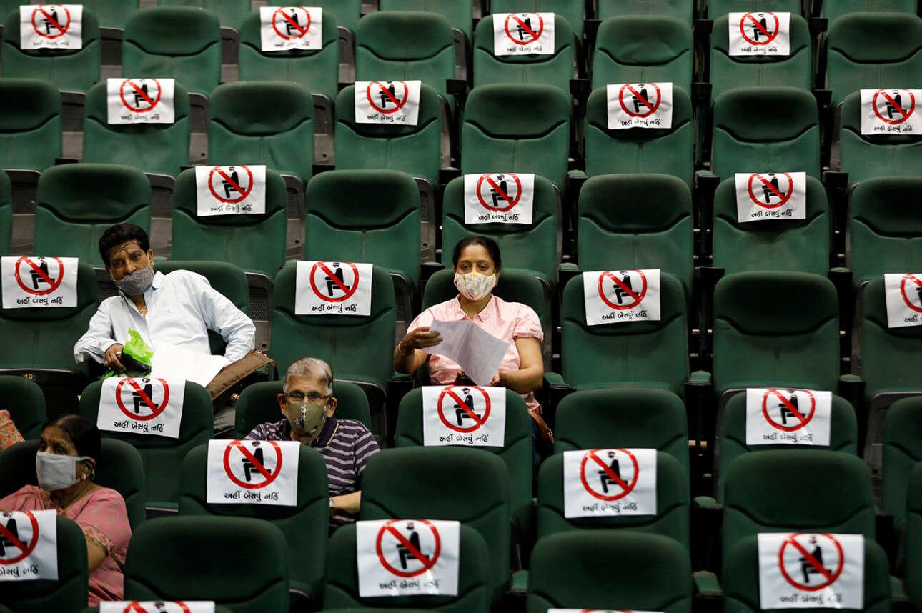 Στo Αχμενταμπάντ της Ινδίας, σε ένα αμφιθέατρο το οποίο έχει μετατραπεί σε προσωρινό κέντρο εμβολιασμού, άνθρωποι παρακολουθούνται μετά τη λήψη μιας δόσης COVISHIELD, του εμβολίου που κατασκευάστηκε από το Serum Institute of India
