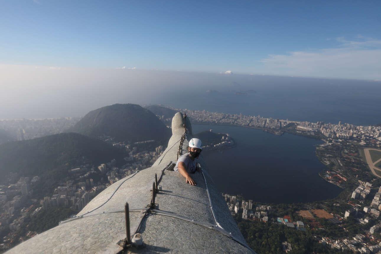 Βραζιλία. Η αρχιτέκτων Κριστίναν Βεντούρα ξεπροβάλλει μέσα από το μπράτσο του Χριστού του Ρίο. Επιβλέπει τις εργασίες συντήρησης του τεραστίου αγάλματος που συμπληρώνει 90 χρόνια ζωής πάνω από τις φαβέλες