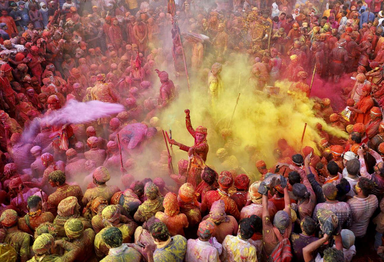 Ινδία. Εορτάζοντες και πανηγυρίζοντες ινδουιστές ρίχνουν χρωματισμένες σκόνες ο ένας στον άλλον