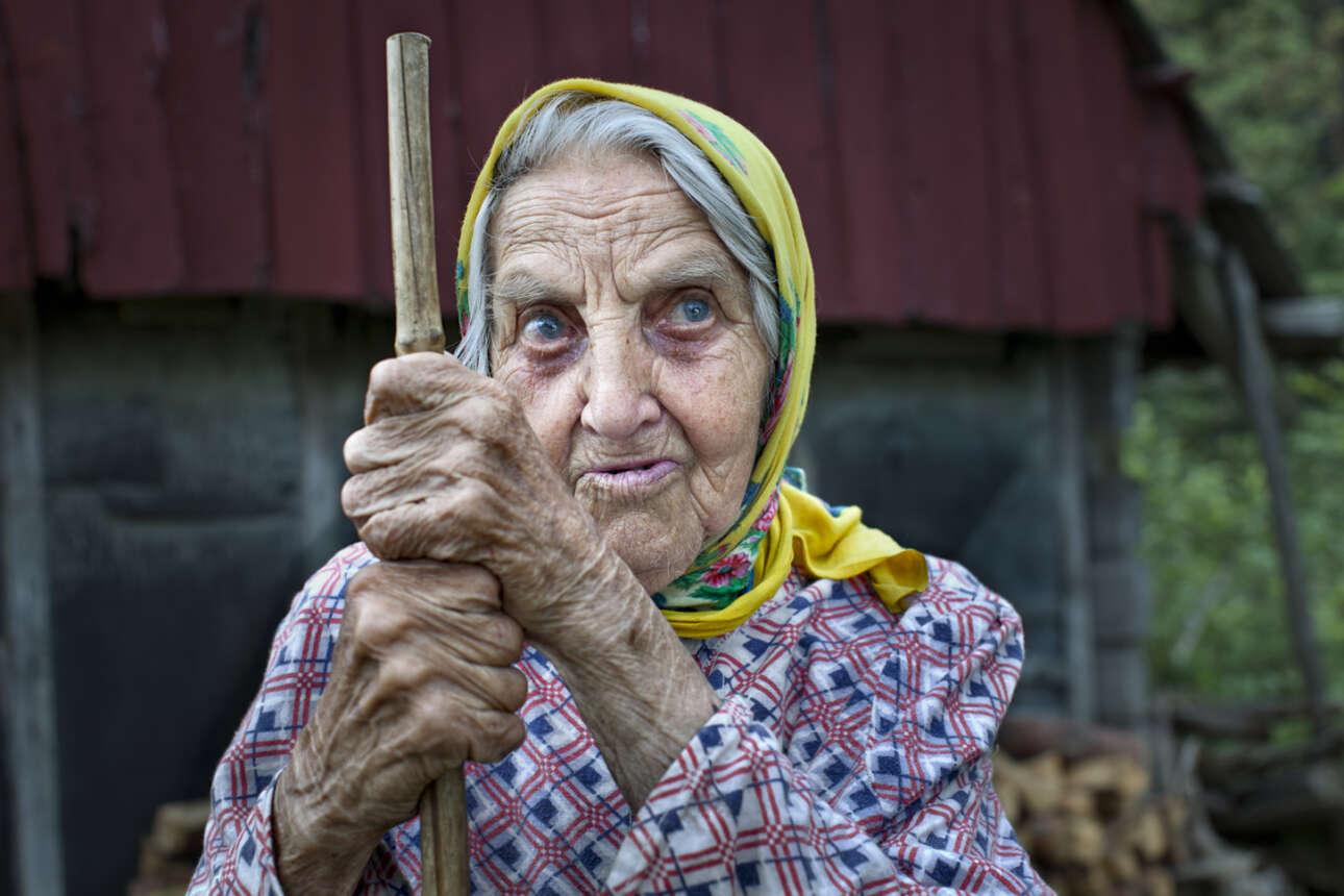 """Εγραψε η φωτογράφος: «Την παρατήρησα σχεδόν να διαλογίζεται πάνω από τον τάφο της οικογένειας της. """"Σύντομα κι εγώ θα είμαι εδώ"""" μου είπε. Μέσω διερμηνέα ρώτησα αν μπορούσα να την ακολουθήσω στο σπίτι της και σαν ένα νεαρό κορίτσι έτρεξε στα χωράφια και στο δάσος. Μόνοι στη μικρή αγροικία της, επικοινωνήσαμε κυρίως με χειρονομίες. Η βαθιά θλίψη από μια πολύ σκληρή ζωή την είχε σημαδέψει. Αργότερα έμαθα για τον αγώνα της ζωής της. Ως νεαρή γυναίκα στη Ρωσία, διατάχθηκε να εργαστεί στο δάσος. Έπρεπε να πάρει το μικρό της γιο μαζί της και ένα δέντρο έπεσε πάνω του. Το τελευταίο πορτραίτο της έγινε η υπογραφή του έργου"""