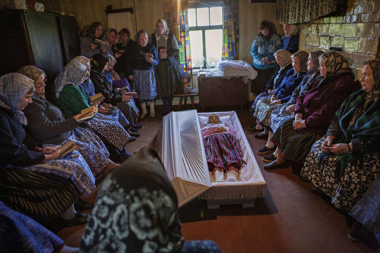 Εγραψε η φωτογράφος: «Είδα την Koksi Leida λίγες ώρες αφότου πέθανε στο δωμάτιό της. Οι γείτονές της με έντυσαν με μπλε ρούχα πένθους και με κάλεσαν να φωτογραφήσω την ιδιωτική τελετή στην κουζίνα. Οι γυναίκες του χωριού συγκεντρώθηκαν γύρω από το φέρετρο για να προσευχηθούν, να πενθήσουν και να τραγουδήσουν. Μετά από λίγο καιρό, οι άντρες ήρθαν και αυτοί να την αποχαιρετήσουν. Στη συνέχεια, το φέρετρο έκλεισε και η Κόκσι Λέιδα άφησε το σπίτι της για τελευταία φορά. Στη συνέχεια οι γυναίκες τακτοποίησαν το τραπέζι στην κουζίνα για ένα παραδοσιακό γεύμα»