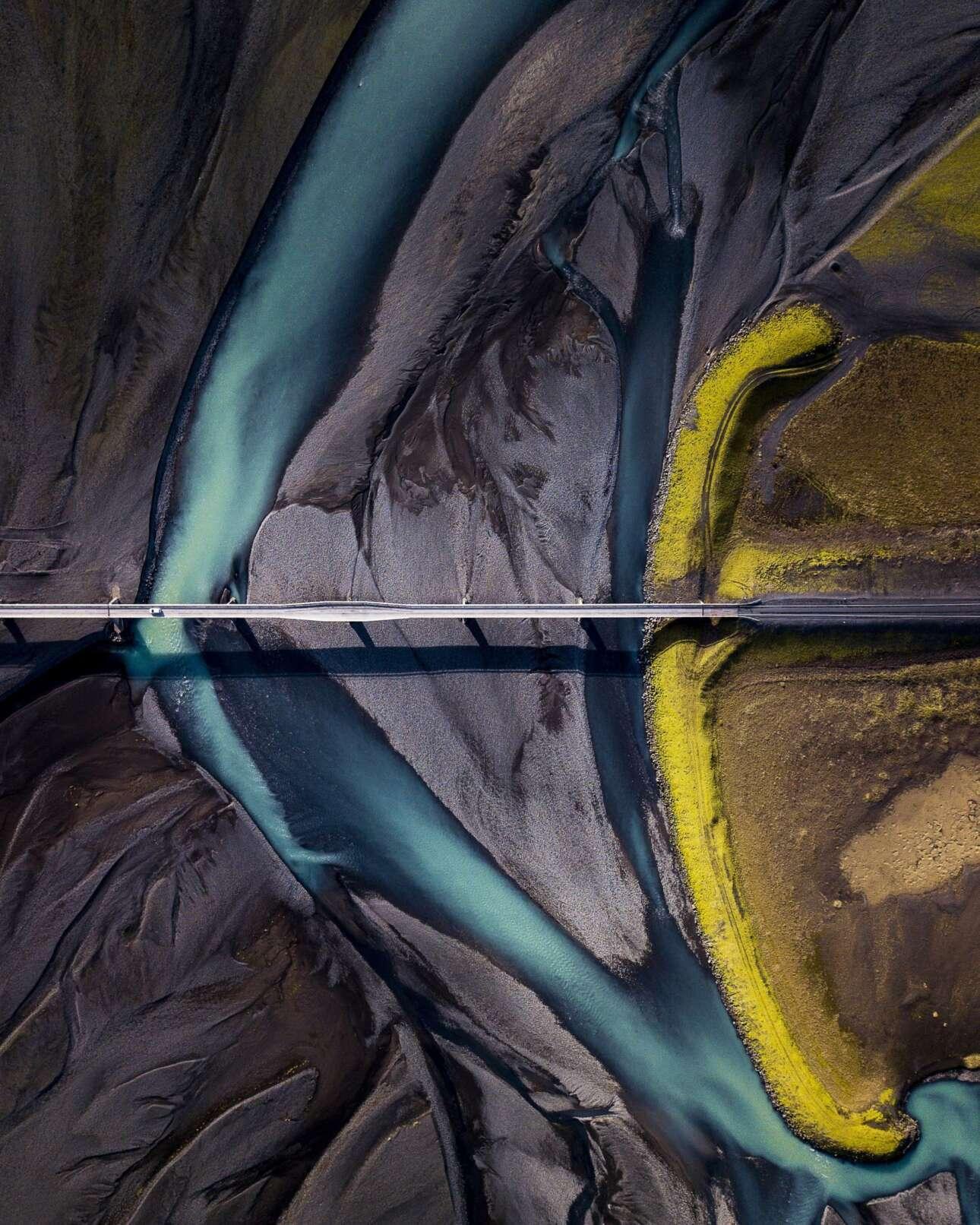 «Συμβίωση», φιναλίστ στην κατηγορία Γραφικό Τοπίο. Ενα πανέμορφο τοπίο στα βουνά  Lómagnúpur της Ισλανδίας, όπου το μπλε ποτάμι έρχεται σε αντίθεση με τη μαύρη άμμο