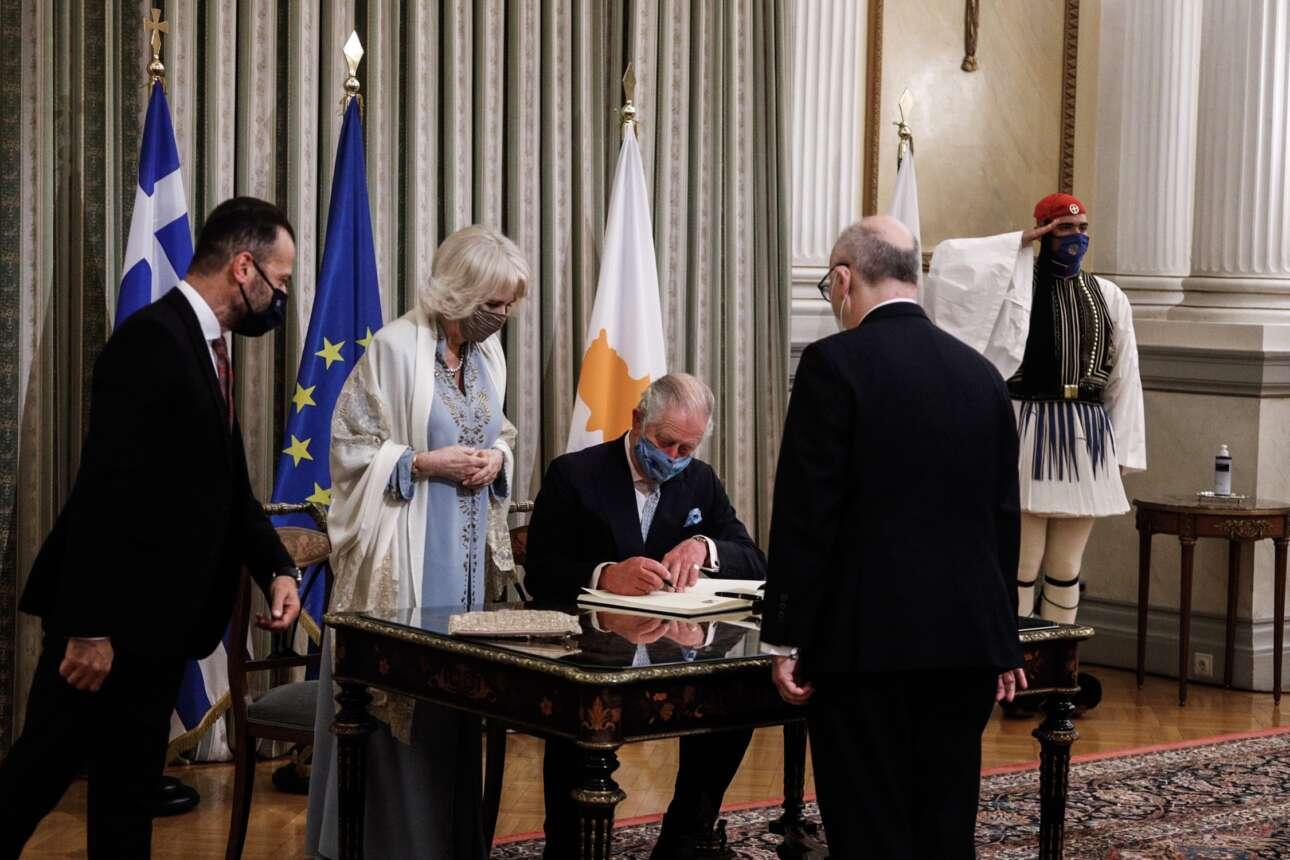 Ο πρίγκιπας Κάρολος, υπό το βλέμμα της συζύγου του, υπογράφει στο βιβλίο επισκεπτών