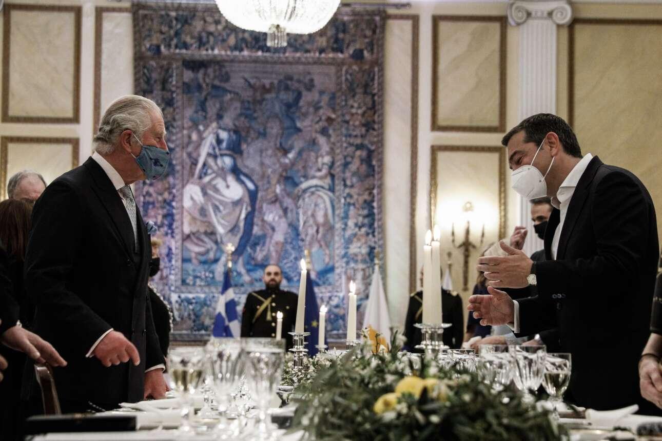 Ο πρίγκιπας Κάρολος σε ένα στιγμιότυπο με τον πρόεδρο του ΣΥΡΙΖΑ Αλέξη Τσίπρα.  Ο πρόεδρος του ΣΥΡΙΖΑ, πάντα χωρίς γραβάτα, εμφανίστηκε στο Προεδρικό χωρίς τη σύντροφό του Μπέτυ Μπαζιάνα, η οποία δικαιολογήθηκε ότι δεν ήταν εμβολιασμένη