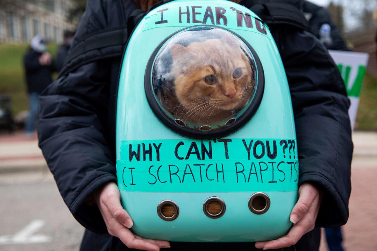 ΗΠΑ. Ο κάτοχος (ή η κάτοχος) του σακιδίου διαδηλώνει στο Μίσιγκαν κατά της σεξουαλικής και πάσης άλλης βίας. Η γάτα θέλει κάτι να του (ή της) πει επ' αυτού, αλλά η κλεισούρα δεν της το επιτρέπει