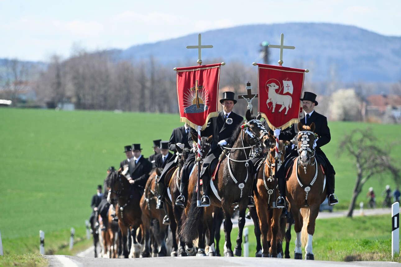 Εορτασμός του Πάσχα των Καθολικών στη Γερμανία: αυτοί οι σλαβόφωνοι καβαλάρηδες φορούν φράκα και κρατούν λάβαρα με θέμα τον Αμνό και την Ανάσταση, αλλά και τον Εσταυρωμένο