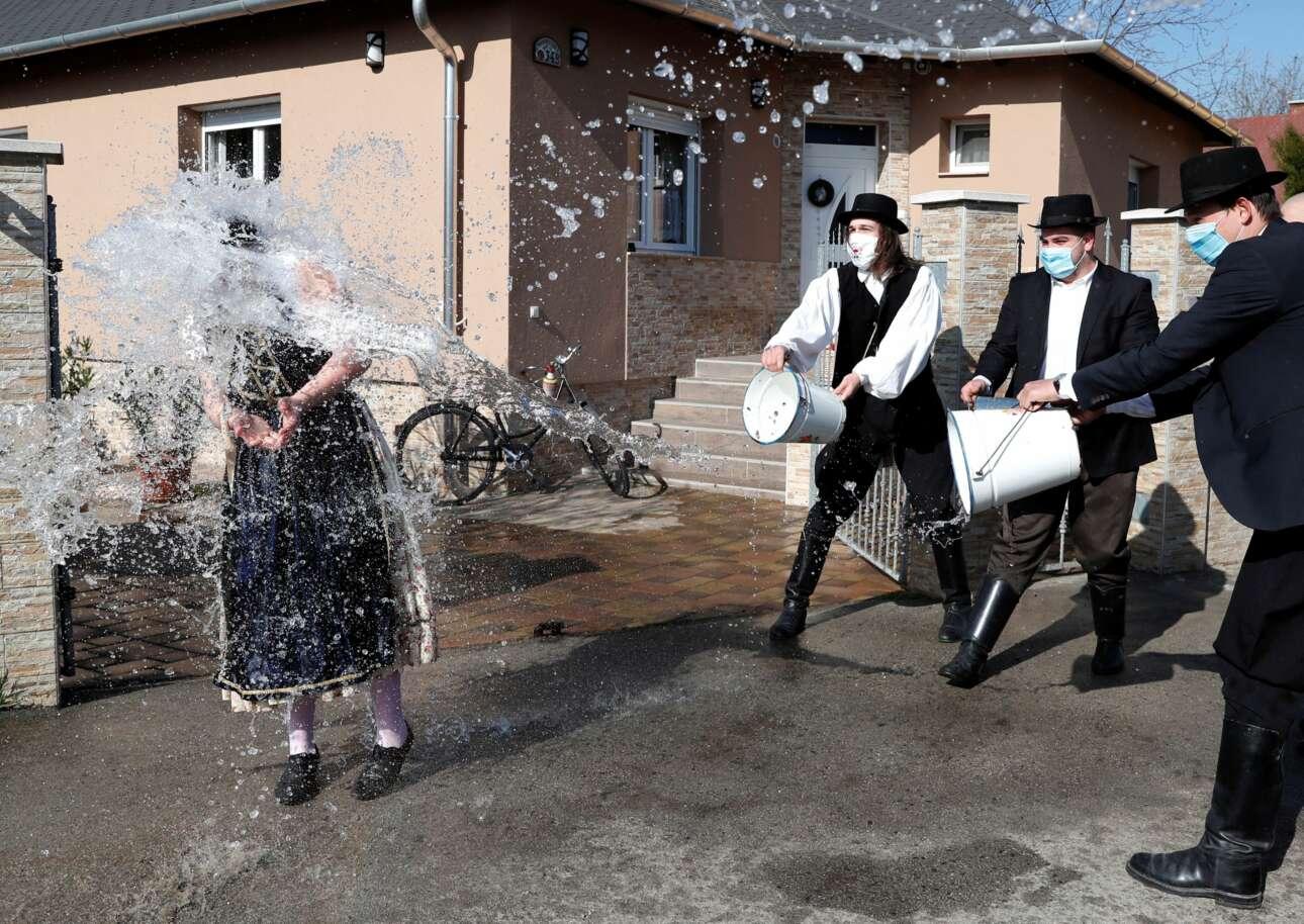 Εορτασμός του Πάσχα των Καθολικών στην Ουγγαρία: μέλη λαογραφικού και χορευτικού συνόλου καταβρέχουν με κουβάδες μία γυναίκα, σε ένα από τα παραδοσιακά τους «δρώμενα»