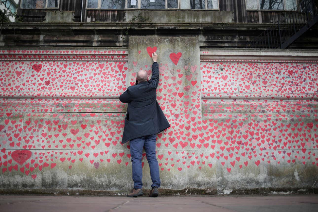 Ενας Λονδρέζος κάτι γράφει στον τοίχο του Εθνικού Μνημείου για τη νόσο Covid-19, που δημιουργήθηκε δίπλα στο νοσοκομείο Σεντ Τόμας εις μνήμην όσων Βρετανών πέθαναν από τον κορονοϊό