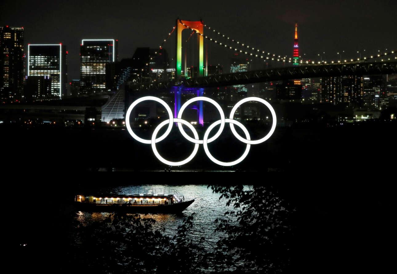Ιαπωνία. Ολυμπιακούς Αγώνες… περασμένης χρονιάς θα φιλοξενήσει εφέτος το Τόκιο – μία πρωτοτυπία που τη χρωστάμε στον κορονοϊό και θα τη θυμόμαστε. Οι φωταγωγήσεις των χαρακτηριστικών σημείων της ασιατικής μεγαλούπολης σηματοδοτούν την αντίστροφη μέτρηση των 100 ημερών μέχρι την έναρξη