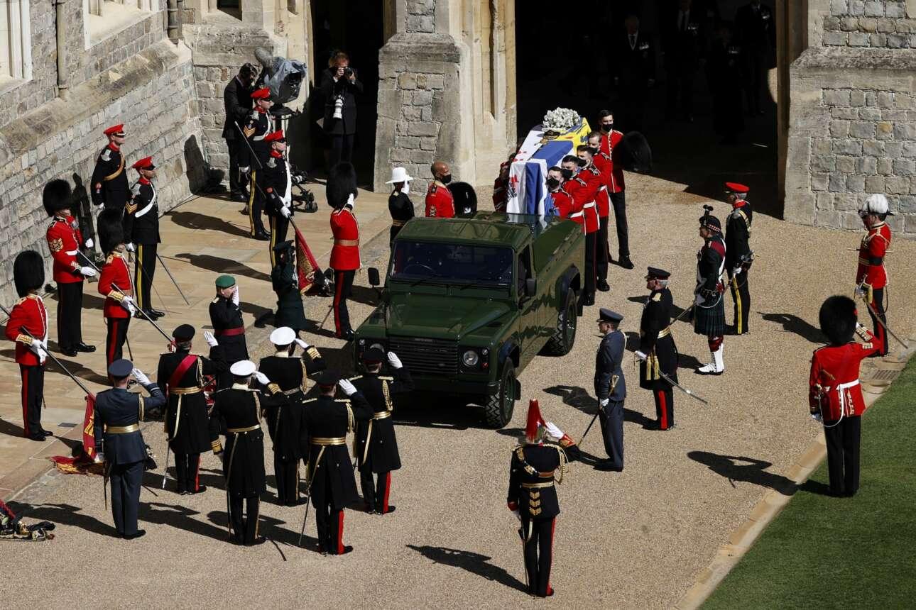 Το φέρετρο του πρίγκιπα Φιλίππου, τυλιγμένο με μία σημαία στην οποία υπάρχουν και τα ελληνικά χρώματα, μπαίνει στο Land Rover Defender TD5 130. Πρόκειται για το όχημα που ο ίδιος είχε επιλέξει να τον οδηγήσει στην τελευταία του κατοικία