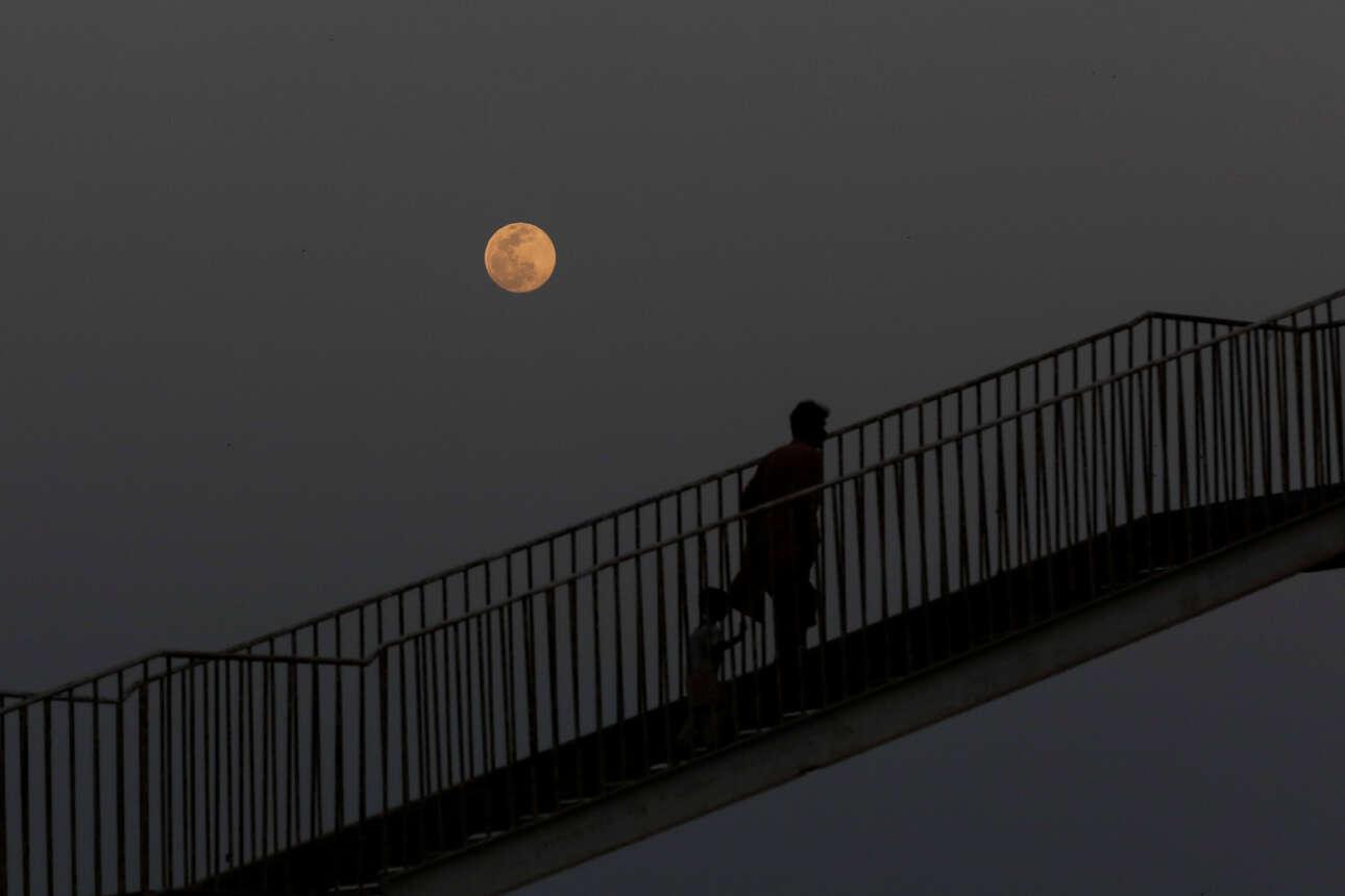 Ανδρας με το παιδί του διασχίζει μια γέφυρα πεζών στο Καράτσι του Πακιστάν, καθώς η υπερ-Σελήνη ανατέλλει στο βάθος