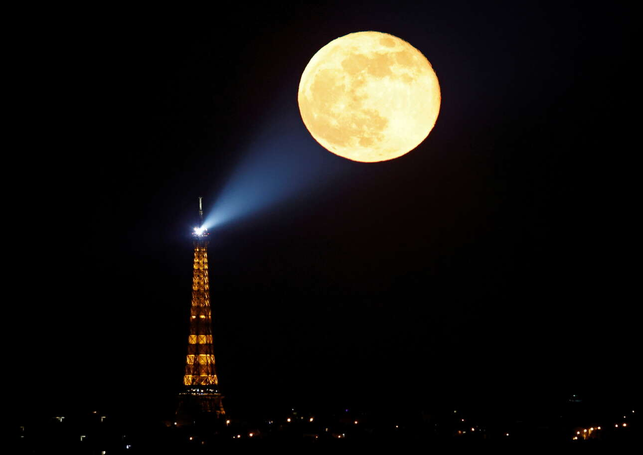 Παρίσι. Παιχνιδιάρικο και φιλόδοξο καρέ με τον Πύργο του Αϊφελ και τη «ροζ» πανσέληνο του Απριλίου: το φεγγάρι σαν να μοιάζει να φωτίζεται από τον προβολέα