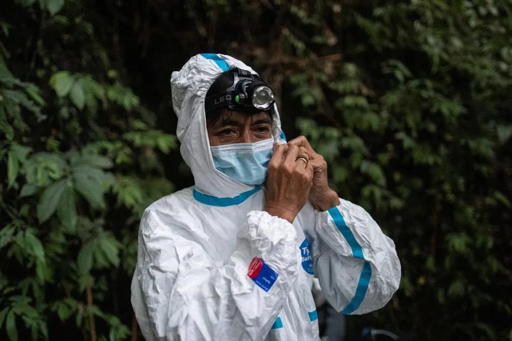 Ο Εντισον Κοσίκο, ένας από τους ερευνητές, φοράει την προστατευτική του στολή. «Ποτέ δεν ξέρεις αν μια νυχτερίδα είναι ήδη φορέας. Ψάχνουμε να δούμε αν υπάρχουν και άλλοι ιοί που μπορεί να μεταδώσουν οι νυχτερίδες στους ανθρώπους. Δεν μπορούμε να ξέρουμε αν ένας από αυτούς θα αποδειχθεί παρόμοιος με αυτόν που προκάλεσε την πανδημία», λέει