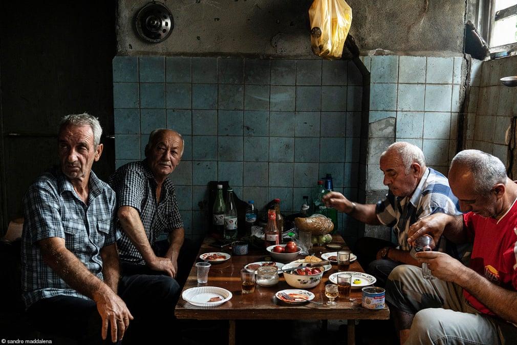 Πολιτική του φαγητού: «Παλιοί Φίλοι». Πρόσφυγες μετά τις συγκρούσεις Αμπχαζίας-Γεωργίας συγκεντρώνονται στο υπόγειο ενός εγκαταλελειμμένου σανατόριου για να μοιραστούν το φαγητό τους. Σχεδόν 30 χρόνια μετά τη σύγκρουση, οι πρόσφυγες της Αμπχαζίας εξακολουθούν να ζουν πάμπτωχοι σε εγκαταλελειμμένα κτίρια