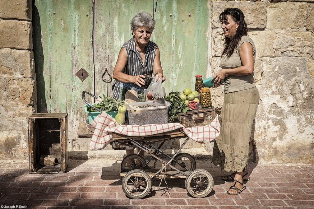 Βραβείο Winterbotham Darby για Τρόφιμα προς Πώληση: «Πωλήτρια στον Δρόμο» του Τζόζεφ Σμιθ, Μάλτα. Μια γυναίκα πουλάει κάπαρη και άλλες λιχουδιές απλωμένες στο παλιό καροτσάκι της, στο ψαροχώρι Μαρσαξλόκ, στη Μάλτα