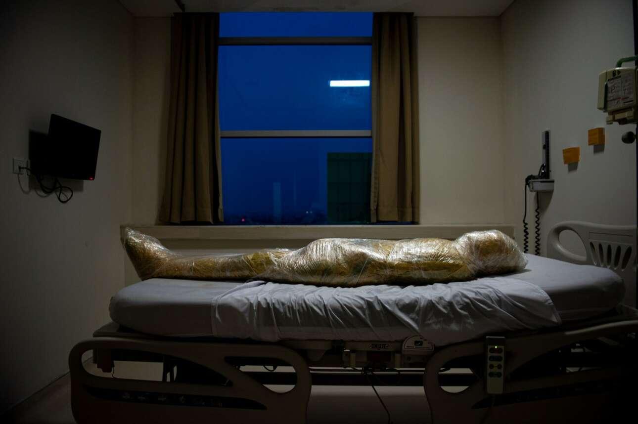 Ινδονησία. «Πακέτο» έκαναν στο νοσοκομείο τον πεθαμένο από κορονοϊό, αφού τον τύλιξαν με το κιτρινωπό ζελατινώδες υλικό που χρησιμοποιούν για την απόρριψη μολυσματικών αποβλήτων. Οι συγγενείς του δεν τον αποχαιρέτησαν καν («Ειδήσεις», δεύτερο βραβείο)