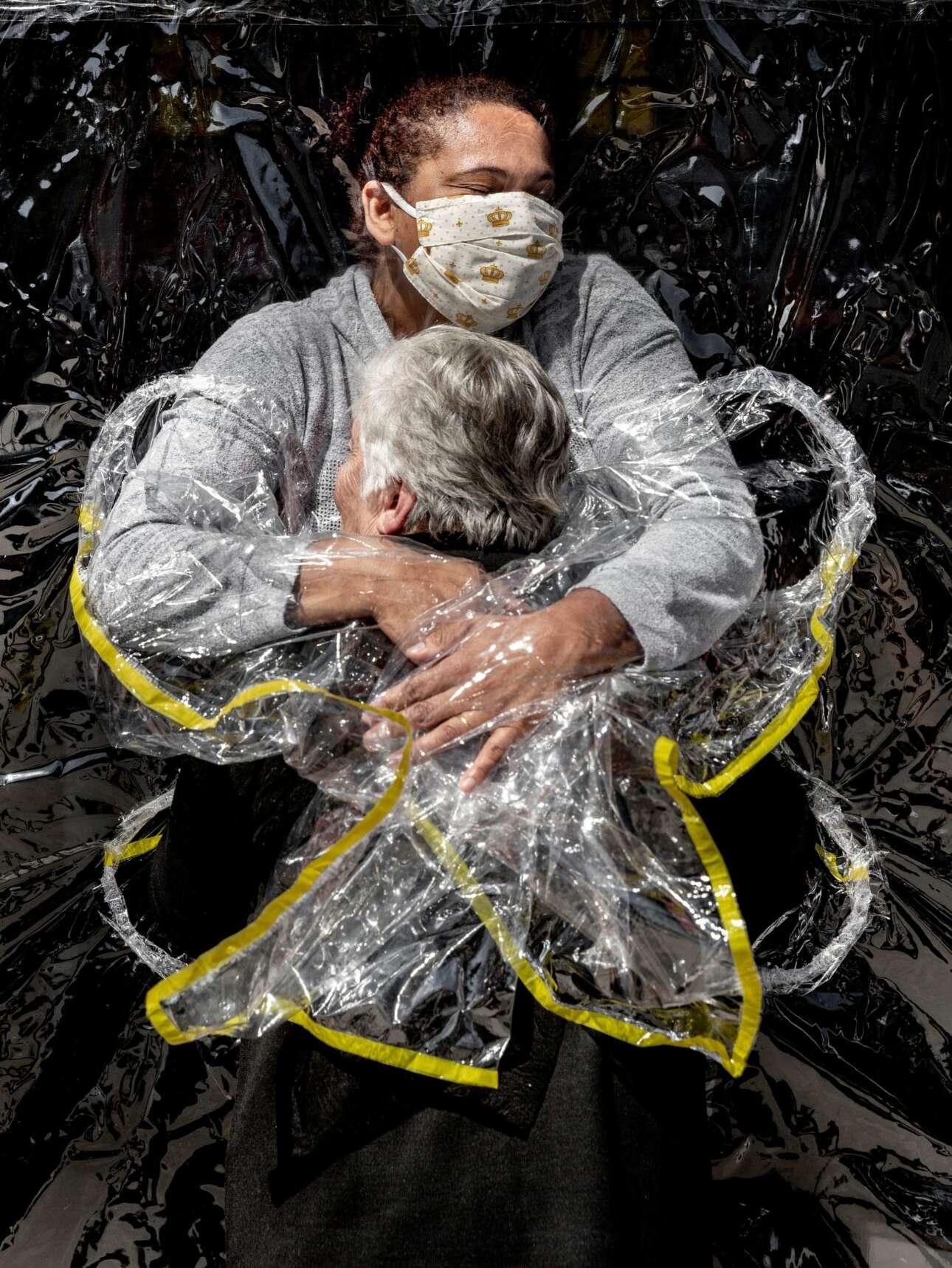 Βραζιλία. Η νοσοκόμα αγκαλιάζει τη γηραιά κυρία, οικότροφο του οίκου ευγηρίας. Αναγκαία σωματική επαφή, πίσω από προστατευτικό πλαστικό παραπέτασμα βέβαια, ύστερα από μερικούς μήνες απόστασης («Φωτογραφία της χρονιάς»)