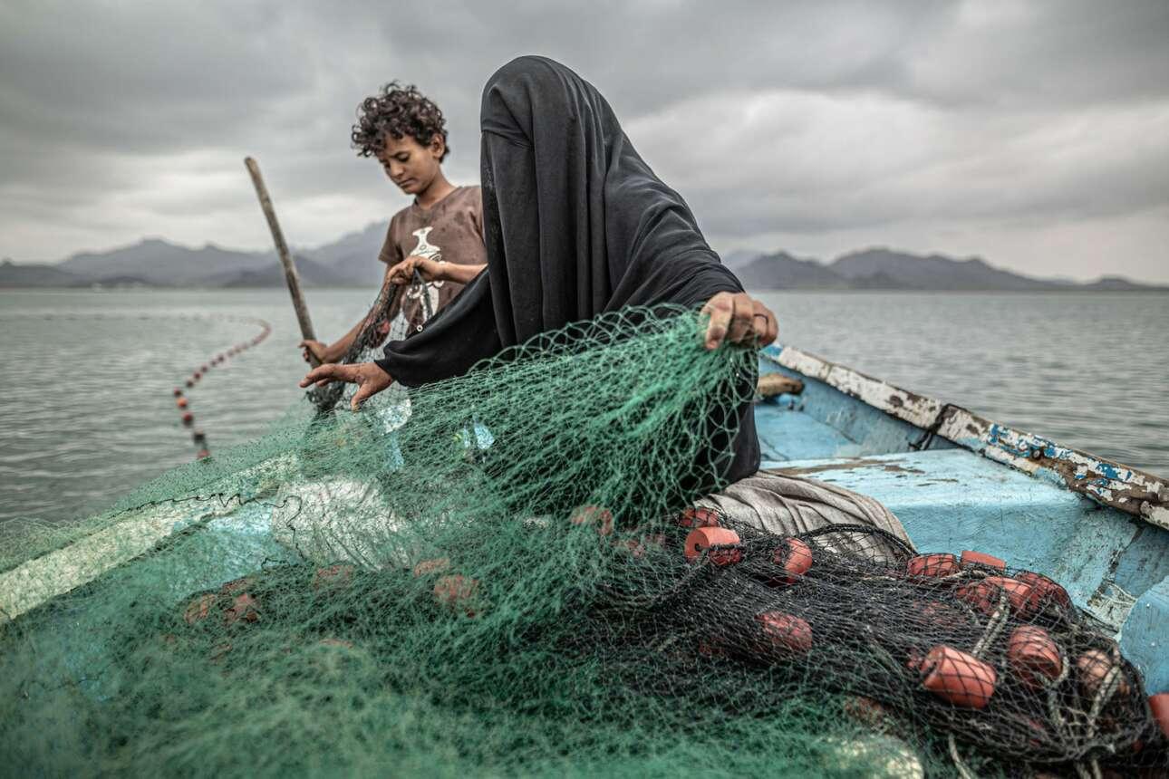Υεμένη. Ναι, κάτω από αυτό το μαύρο πανί υπάρχει άνθρωπος – γυναίκα. Εμείς μπορούμε να δούμε μόνο το πρόσωπο του γιου της. Οι δυο τους ετοιμάζονται να ψαρέψουν, αφού από το ψάρεμα ζουν στην κατεστραμμένη από τον μουσουλμανικό εμφύλιο χώρα («Σύγχρονα θέματα», πρώτο βραβείο)